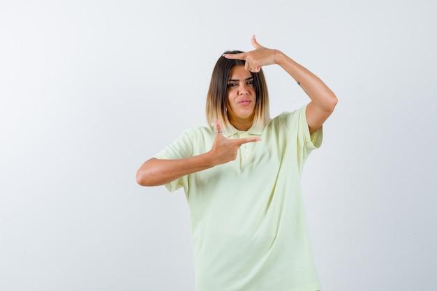 Młoda dziewczyna pokazuje gest ramy w koszulce i wygląda poważnie. przedni widok.
