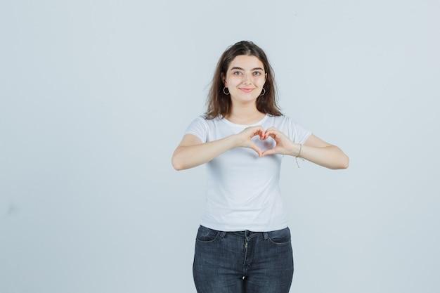 Młoda dziewczyna pokazuje gest serca w t-shirt, dżinsy i patrząc szczęśliwy, widok z przodu.