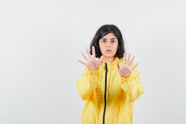 Młoda dziewczyna pokazuje gest stop obiema rękami w żółtej kurtce bombowej i wygląda poważnie