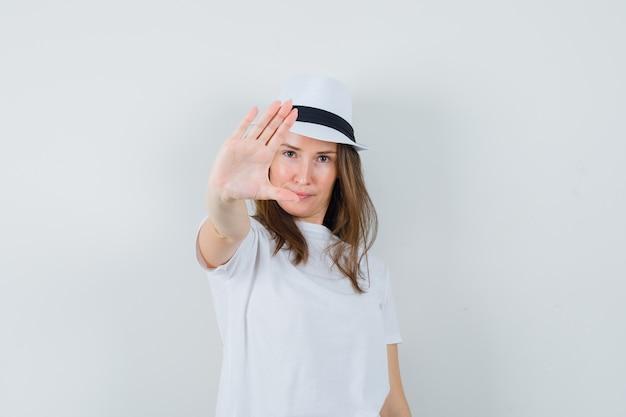 Młoda dziewczyna pokazuje gest stop w białym kapeluszu t-shirt i wygląda pewnie