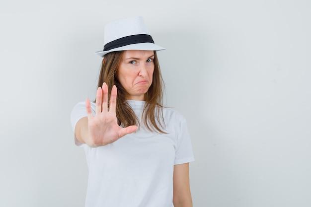 Młoda dziewczyna pokazuje gest stopu w białym kapeluszu t-shirt i wygląda na zirytowanego