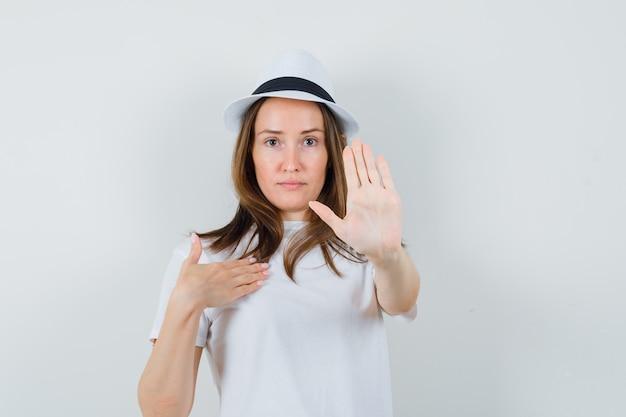 Młoda dziewczyna pokazuje gest stopu w kapeluszu biały t-shirt i szuka stanowczy