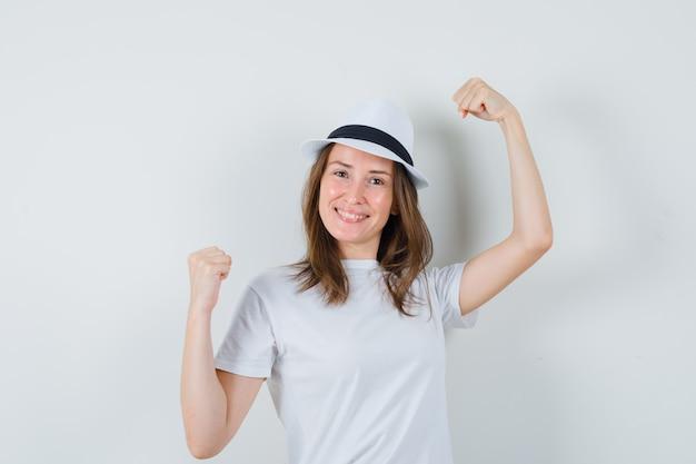 Młoda dziewczyna pokazuje gest zwycięzcy w kapeluszu biały t-shirt i szuka szczęścia
