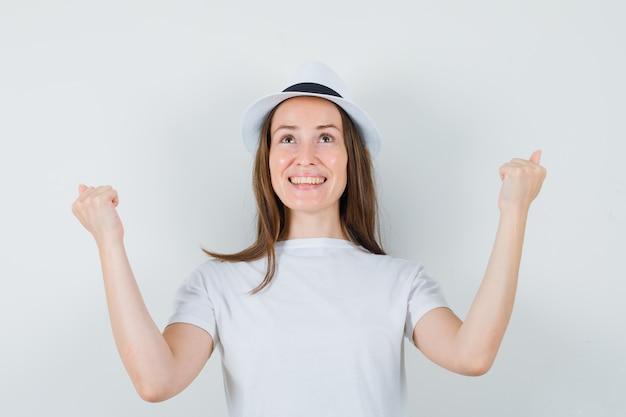 Młoda dziewczyna pokazuje gest zwycięzcy w kapeluszu biały t-shirt i wygląda błogo