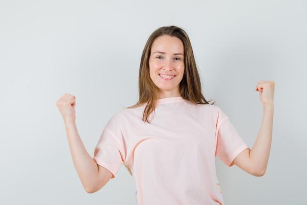 Młoda dziewczyna pokazuje gest zwycięzcy w różowej koszulce i wygląda radośnie