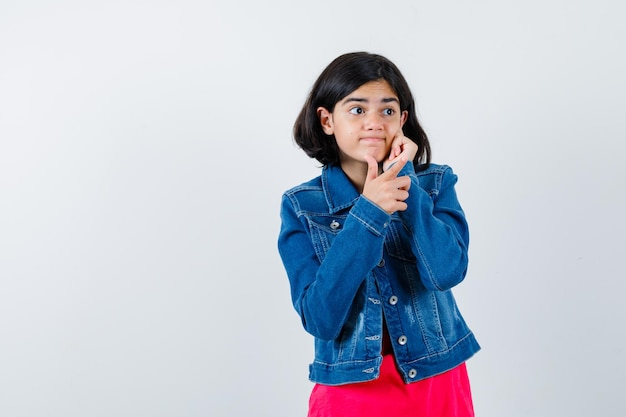 Młoda dziewczyna pokazuje kciuk i pochylony policzek na dłoni w czerwoną kurtkę t-shirt i dżinsową i wyglądający szczęśliwy. przedni widok.