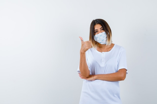 Młoda dziewczyna pokazuje kciuk, trzymając rękę pod łokciem w białej koszulce i masce i wygląda pewnie. przedni widok.