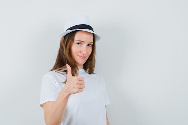Młoda dziewczyna pokazuje kciuk w białym kapeluszu t-shirt i wygląda pewnie