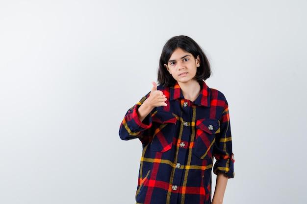 Młoda dziewczyna pokazuje kciuk w kraciaste koszule i wygląda na szczęśliwą. przedni widok.