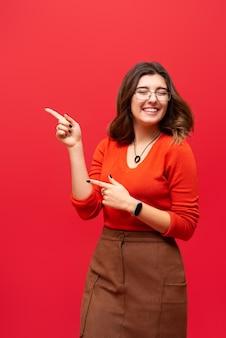 Młoda dziewczyna pokazuje kciuki do góry na czerwonej ścianie