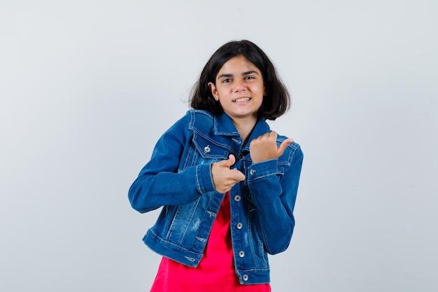 Młoda dziewczyna pokazuje kciuki do góry obiema rękami w czerwonej koszulce i kurtce dżinsowej i wygląda na szczęśliwą. przedni widok.