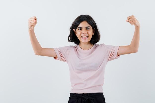 Młoda dziewczyna pokazuje mięśnie w różowej koszulce i czarnych spodniach i wygląda na szczęśliwą