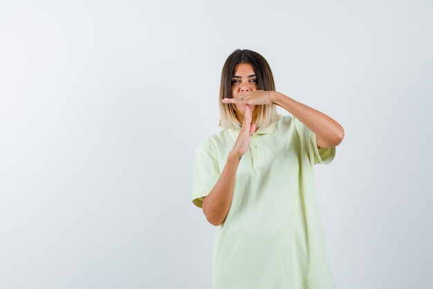 Młoda dziewczyna pokazuje przerwę gest w koszulce i wygląda poważnie. przedni widok.