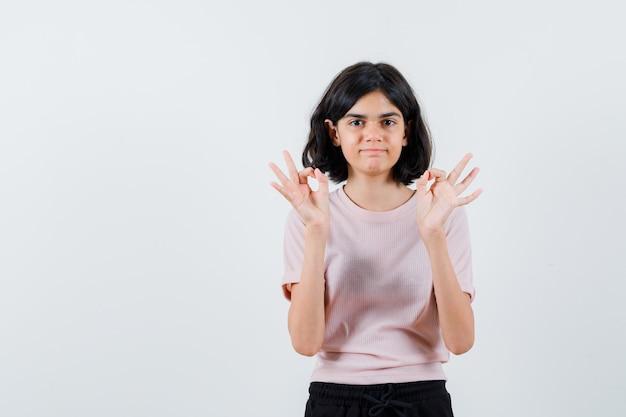 Młoda dziewczyna pokazuje znak ok obiema rękami w różowej koszulce i czarnych spodniach i wygląda na szczęśliwą