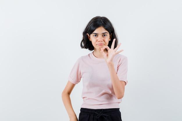 Młoda dziewczyna pokazuje znak ok w różowej koszulce i czarnych spodniach i wygląda na szczęśliwą