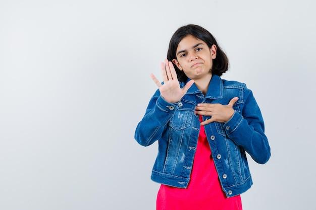 Młoda dziewczyna pokazuje znak stop w czerwony t-shirt i kurtka dżinsowa i wygląda poważnie. przedni widok.