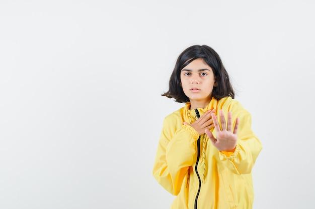 Młoda dziewczyna pokazuje znak stopu w żółtej bomberce i wygląda poważnie