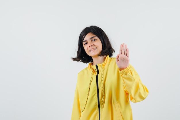 Młoda dziewczyna pokazuje znak stopu w żółtej kurtce bombowej i wygląda na szczęśliwego.
