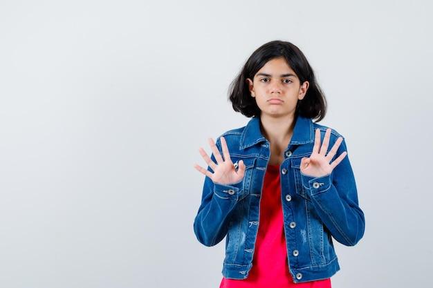 Młoda dziewczyna pokazuje znaki stop w czerwonej koszulce i kurtce dżinsowej i patrząc poważnie, widok z przodu.