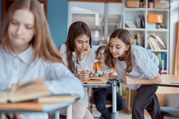 Młoda dziewczyna pomaga czytać kolegę z klasy. dzieci ze szkoły podstawowej siedzą na biurkach i czytają książki w klasie.