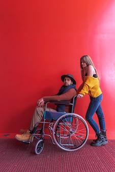 Młoda dziewczyna pomaga niepełnosprawnemu mężczyzna na wózku inwalidzkim