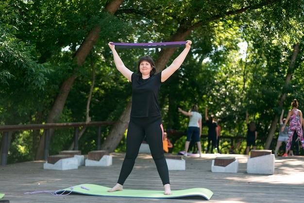 Młoda dziewczyna pompuje ręce za pomocą ekspandera. fitness w parku. trening na ekspanderze dla początkujących. szkolenie indywidualne