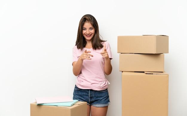 Młoda dziewczyna porusza się w nowym domu wśród pól wskazuje palcem na ciebie