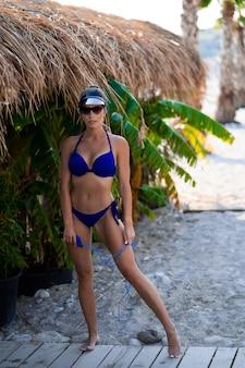 Młoda dziewczyna pozuje na plaży. sportowe szczęśliwa kobieta w modnym niebieskim seksownym stroju kąpielowym, ciesząc się słońcem ćwiczeń. zdrowy tryb życia. doskonałe kształty ciała fitness.