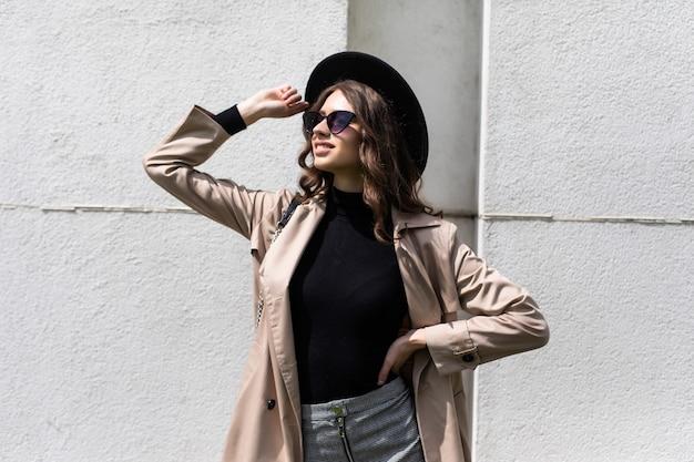 Młoda dziewczyna pozuje na ulicy w słoneczny dzień, sama bawiąc się, stylowy kapelusz vintage ubrania i okulary przeciwsłoneczne. koncepcja podróży