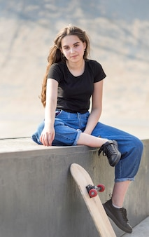 Młoda dziewczyna pozuje obok deskorolki na zewnątrz