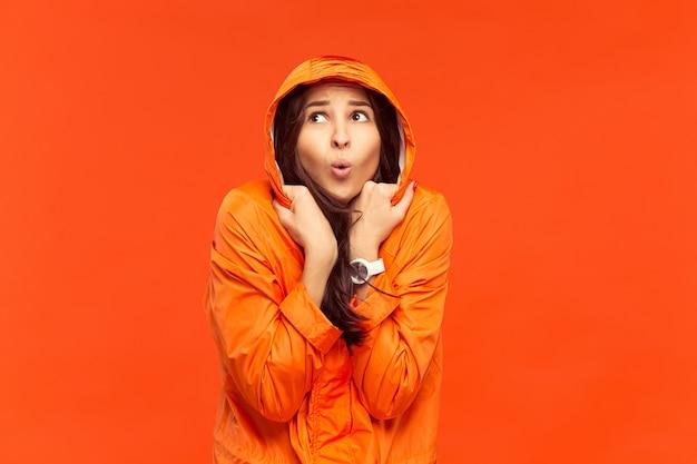 Młoda dziewczyna pozuje w studio w jesiennej kurtce na białym tle na czerwono. ludzkie negatywne emocje. pojęcie zimnej pogody. koncepcje mody kobiecej