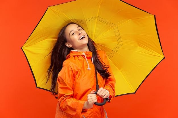 Młoda dziewczyna pozuje w studiu w jesiennej kurtce odizolowywającej na czerwieni