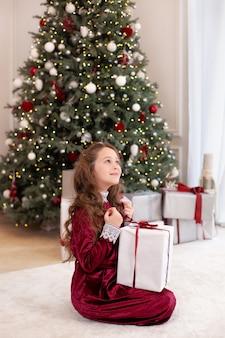 Młoda dziewczyna pozuje z prezentami