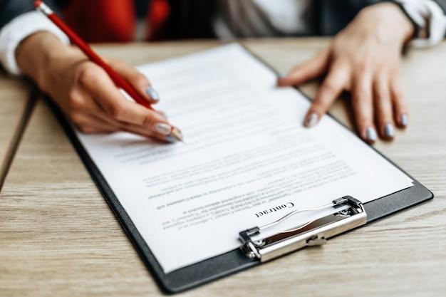 Młoda dziewczyna pracownik biurowy lub biznes pani podpisuje dokumenty.