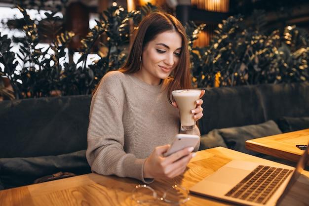 Młoda dziewczyna pracuje na komputerze w kawiarni