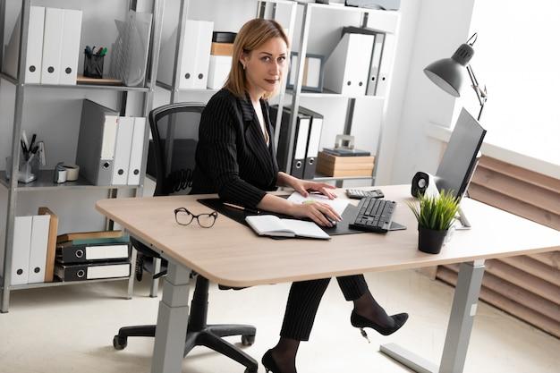 Młoda dziewczyna pracuje w biurze przy biurku komputerowym.