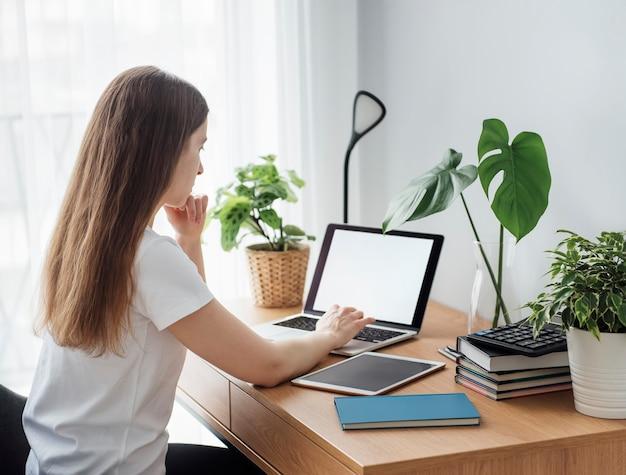 Młoda dziewczyna pracuje w domowym biurze przy stole