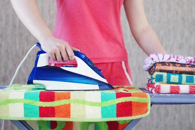 Młoda dziewczyna prasowanie ręczników żelazkiem elektrycznym na desce do prasowania.