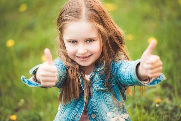 Młoda dziewczyna preteen gestykuluje znaki dłoni