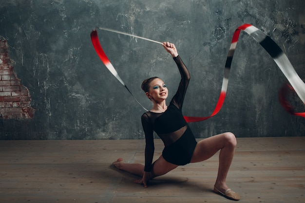 Młoda dziewczyna profesjonalny gimnastyczka kobieta taniec gimnastyka artystyczna ze wstążką w studio.