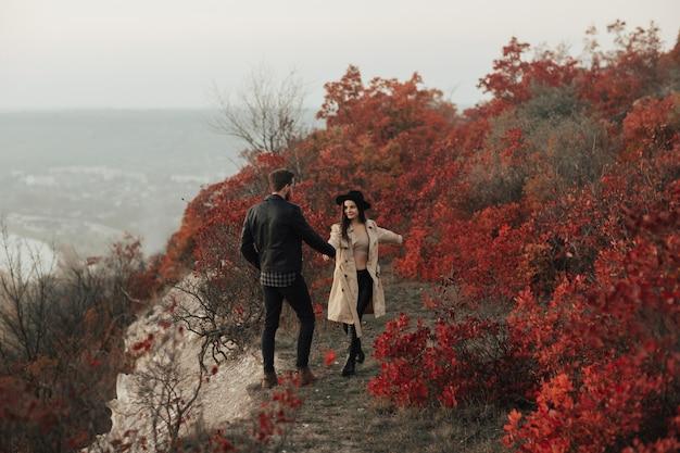 Młoda dziewczyna prowadząc chłopaka do pięknego jesiennego krajobrazu, trzymając go za rękę i uśmiechając się