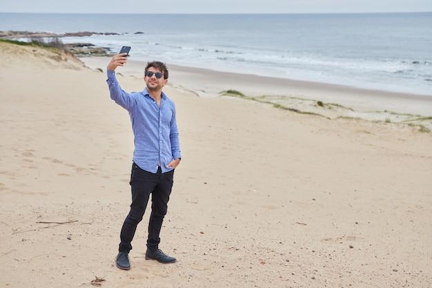 Młoda dziewczyna przy selfie na plaży. podczas gdy dzień jest pochmurny i można zobaczyć piękny piasek i morze.