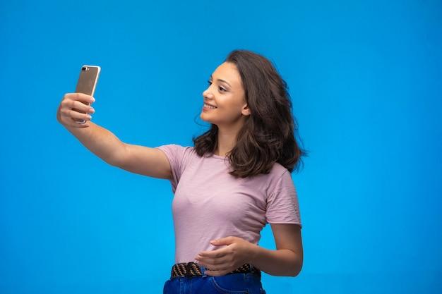 Młoda dziewczyna przy selfie ze swoim smartfonem.
