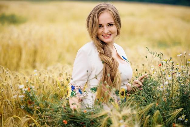 Młoda dziewczyna przy ukraińską obywatel suknią pozującą przy wianku polem.