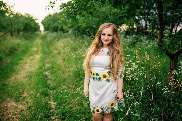 Młoda dziewczyna przy ukraińską obywatel suknią pozującą przy wiosna ogródem.