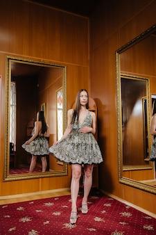 Młoda dziewczyna przymierza nowe ubrania w przymierzalni sklepu.