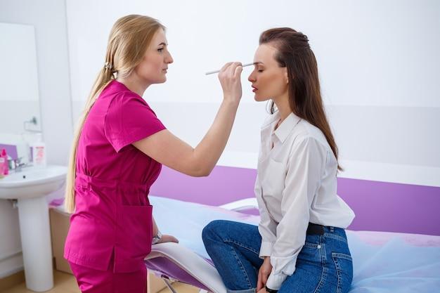 Młoda dziewczyna przyszła do kliniki na wizytę u wykwalifikowanego lekarza, specjalisty kosmetologa. lekarz bada stan skóry na twarzy pacjenta