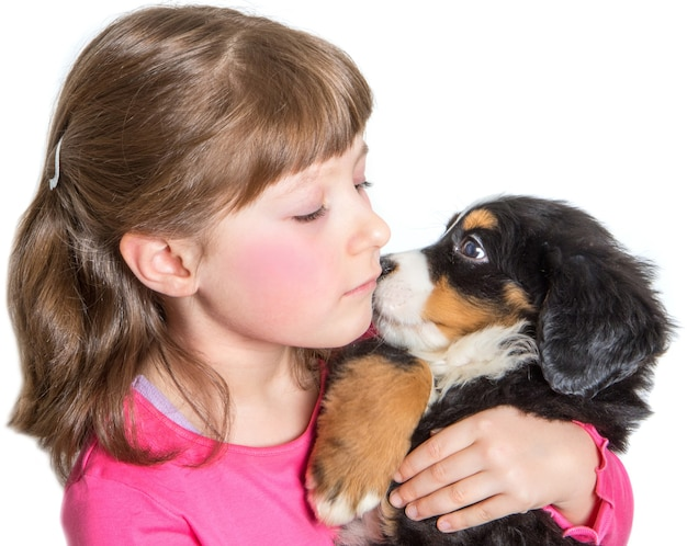 Młoda dziewczyna przytula szczeniaka berneńskiego psa pasterskiego