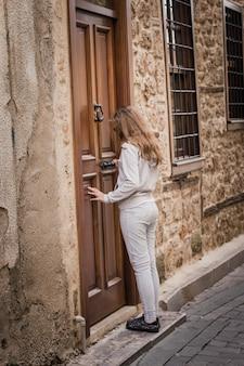 Młoda dziewczyna puka przy starym drewnianym drzwi na wąskiej ulicie stary miasto w antalya