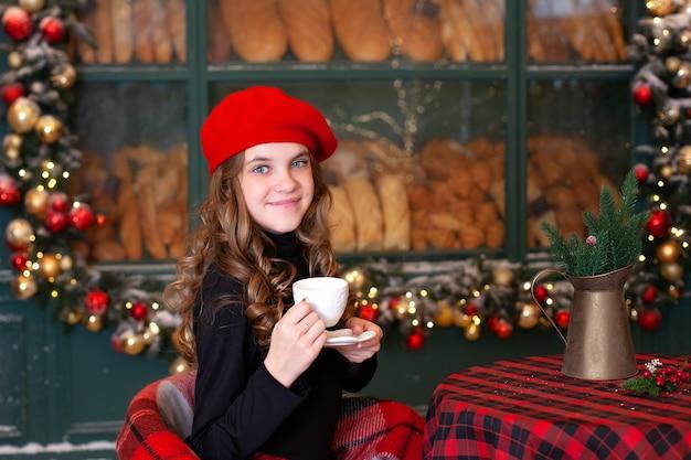 Młoda dziewczyna relaks na tarasie bożego narodzenia cafe, trzymając filiżankę kawy